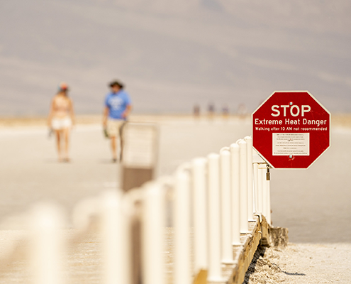 """In foreground, red octagonal sign reads """"STOP Extreme Heat Danger"""" - People walk near beach in background"""